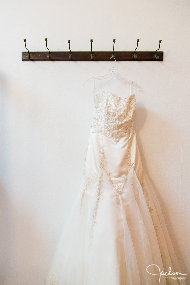 bride's dress hanging from wooden hook