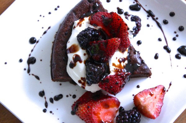 Paleo Flourless chocolate cake with berries, whipped cream and balsamic drizzle