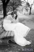 wedding dress model on a park bench