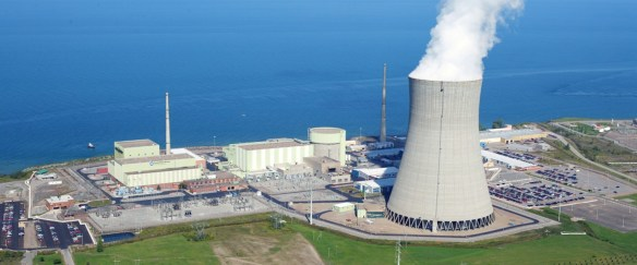A nuclear power plant with the nuclear plant (small rectangle buildings and one cylindrical building) and a cooling tower (big steaming parabolic-shaped tower). Nuclear power plants never shut down, except to change fuel rods.