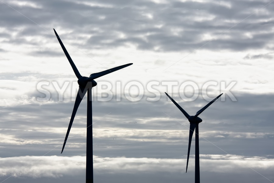 Two windmills grey sky - Jan Brons Stock Images
