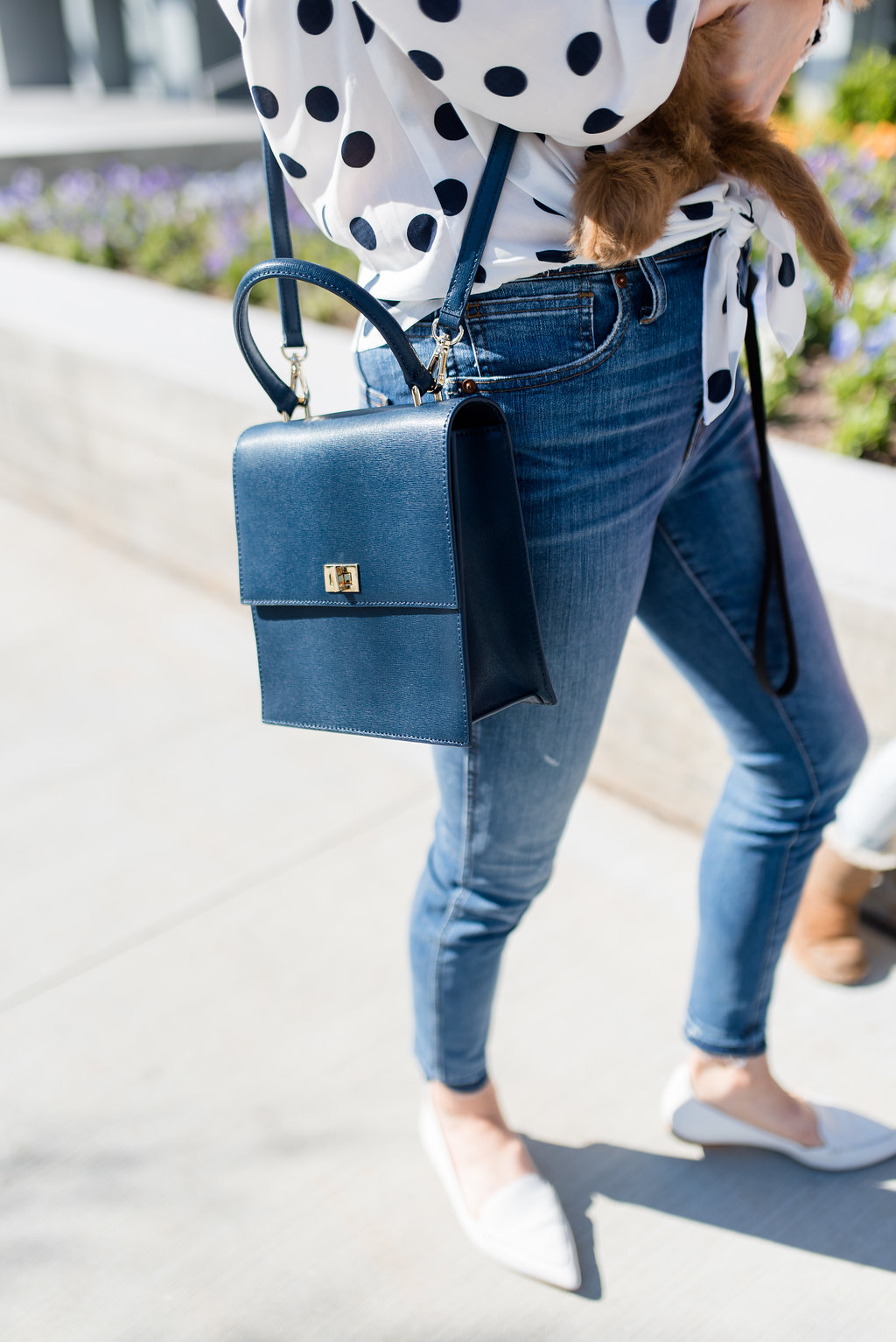 navy cross body bag with jeans and polka dot top