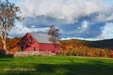 Barn in Maine on an October morning with fall foliage on the hills behind it