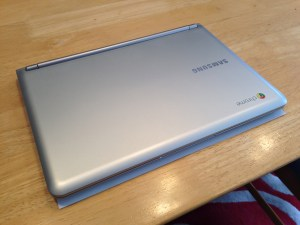 """The Samsung Chromebook on an 8.5"""" x 11"""" sheet of paper."""
