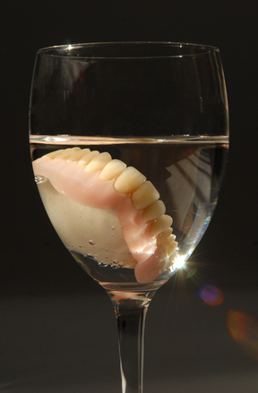 Dentures in a glass of water on black background.