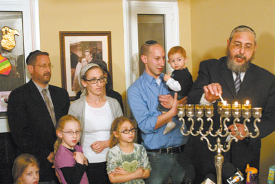 Beit Shemesh City Council Member Rabbi Dov Lipman (far left) and Shas MK Rabbi Chaim Amsalem (far right) light Chanukah candles at the home of the Margolis family on Monday evening. The spitting attack on 8-year-old Na'ama Margolis by a haredi extremist sparked outrage across Israel.
