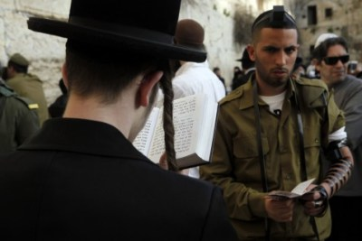 IDF soldier and Haredi man praying at the Western Wall.