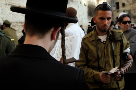 IDF soldier and Haredi man praying at the Western Wall