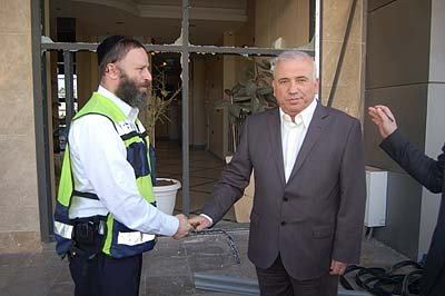Ashdod Deputy Mayor Boris Giterman shakes hands with ZAKA volunteer Yossi Landau in front of the shattered glass doors of a local store.