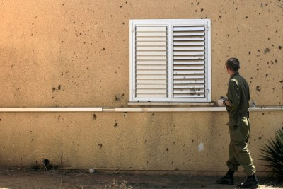 An Israeli army sapper examines a mortar shell damage caused to a house by a mortar shell fired by Palestinian militants from the Gaza Strip