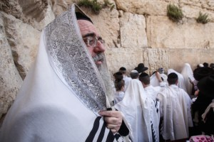 Jewish worshippers cover themselves with prayer shawls as they pray in front of the Western Wall, Judaism's holiest prayer site, in Jerusalem's Old City, during the Cohen Benediction priestly blessing at the Jewish holiday of Passover which commemorates the Israelites' hasty departure from Egypt. April 09, 2012.