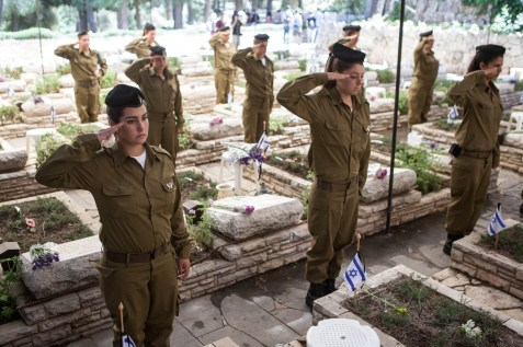 Israeli soldiers gather at the side of graves at the Mount Herzl military cemetery in Jerusalem.