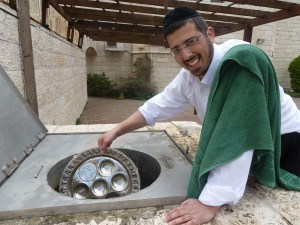 Rabbi Avi Elbaz dunks a new Pesach plate in the ritual bath, preparing for use on the holiday. French Hill, Jerusalem.