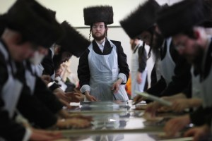 "Ultra-Orthodox Jewish men dressed up with traditional holiday clothes making matzah by hand, a traditional unleavened bread eaten during the Jewish holiday of Passover, just few hours before the ""Seder"" starts. Jews are forbidden to eat leavened foodstuffs during the Passover holiday. The week-long festival commemorates the exodus of the ancient Hebrews from Egypt."