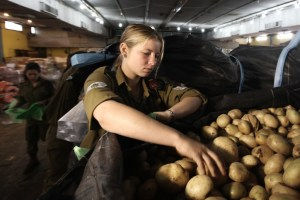 Israeli soldiers prepare food packages at a distribution center for needy in Lud on April 03, 2012, ahead of the Jewish holiday of Passover.