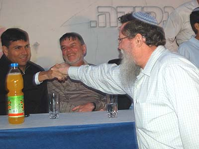 MK Yaakov Katz (Ketzaleh, R.) shaking hands with Likud MK Danny Danon at a recent pro-settlements assembly in Bet El.