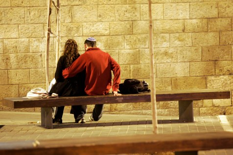 A couple sits on a bench for a few intimate moments