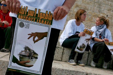 Peace activists holds posters calling to boycott Israel.
