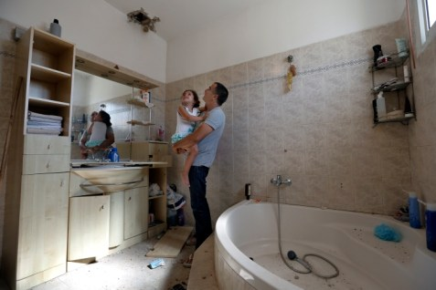 Father and daughter investigate damage to the bathroom in their house in Sderot by a rocket from Gaza.Tsafrir Abayov Flash90