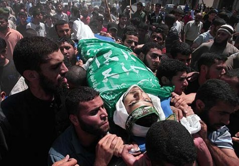 Arabs carry the body of Hamas terrorist Hamam Abu Qadus killed by an Israeli air raid on three Hamas security targets in the Gaza Strip.