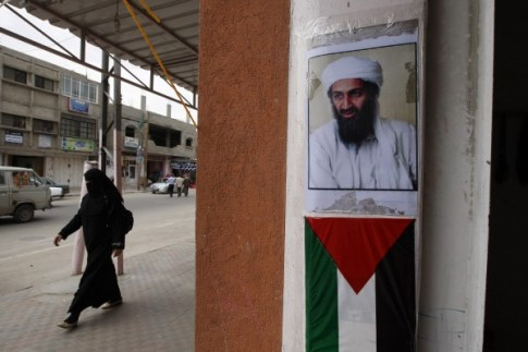 Photo of Al Qaeda founder and former leader, Osama Bin Laden, seen above a Palestinian Authority flag.