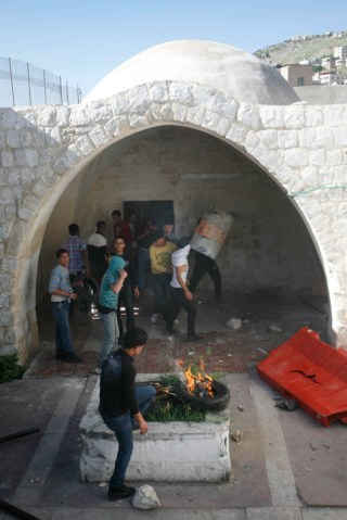 Masked Palestinian youth burn tires and throw stones in Joseph's Tomb.