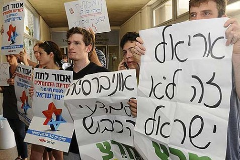 "Left-wing activists reveal the real reason why they, like their professors, want Ariel Dead. Their signs say (right to left): ""Ariel is not Israel,"" ""University for Occupation Sciences,"" and ""Don't let the Settler's State take over the State of Israel."""