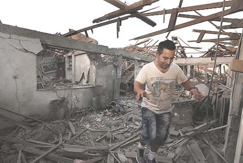 A resident of Netivot walking inside the house that was hit early Sunday morning by a long-range Grad rocket from Gaza.