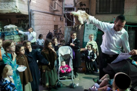 A Jewish man waves a chicken over his head, performing the kaparot ritual, in the neighborhood of Meah Shearim, September 20, 2012.