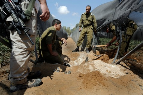 Israeli army soldiers from the bomb squad search for a mortar shell fired from Gaza
