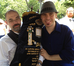 Dr. Joshua Schwimmer, left, and Andrew Schwimmer, carry the Sefer Torah dedicated to their grandparents.