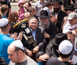 Dr. Richard Schwimmer, accompanied by Rabbi Zushe Winner, carries the Sefer Torah during the Grand Torah Parade.