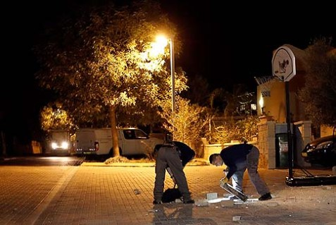 Israeli police explosive experts examines the remains of a rocket that was fired from Gaza and exploded in Kibbutz Kfar Aza, southern Israel, Saturday, Nov. 10, 2012.