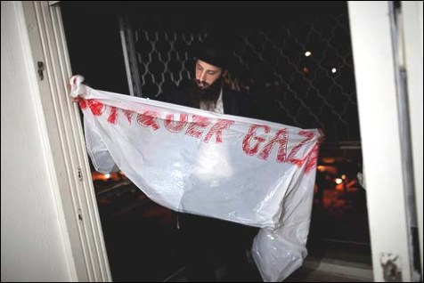 A Haredi man hangs a sign calling to &quot;Conquer Gaza&quot; in his apartment building in Kiryat Malachi which was struck by a grad rocket fired from Gaza killing 3.