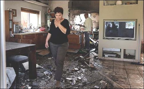 An Israeli woman walking through her home that was hit by a rocked fired from the Gaza Strip.