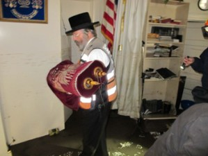 Rabbi Mordechai Jungreis, Nikolsburger Rebbe, salvaging a sefer Torah from a flooded Belle Harbor shul basement.