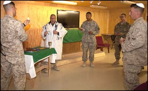 U.S. Navy Lt. Joshua Sherwin, second from left, a Jewish chaplain deployed with II Marine Expeditionary Force (Forward), sings the final hymn and recites the final blessing prior to breaking bread and sharing wine in fellowship with worshippers attending a Yom Kippur service Oct. 8, 2011, at Camp Leatherneck in Helmand province, Afghanistan.