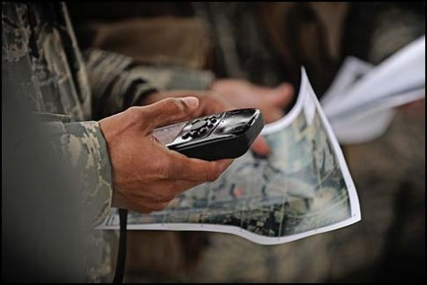 Trainees study their maps and GPS devices during the land navigation portion of their survival, evasion, resistance and escape training at Scott Air Force Base, Ill.