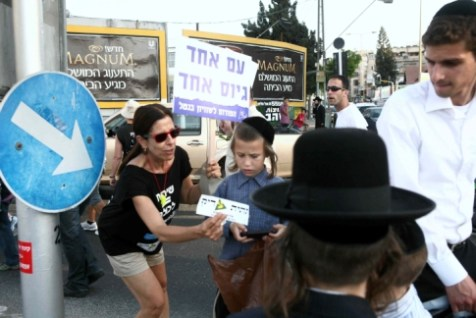 A Secular woman handing a Hareidi child a &quot;Universal Draft&quot; sticker during a protest.