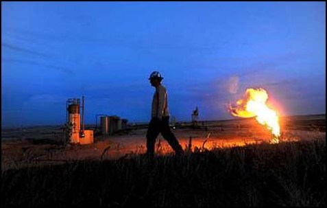 A natural gas flare illuminates an oil well at dusk in Williston, North Dakota.