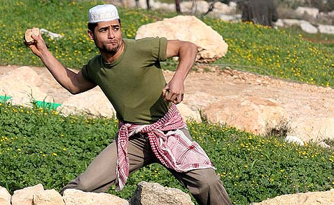 Arab throwing a stone at a Jewish target. (illustrative / archive)
