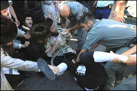 Haredi men scuffle with Israeli police.