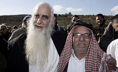 Menachem Froman (L), stood with copies of the Koran at a roadblock outside the village of Yasuf, near Shchem, December 13, 2009, after copies of the Koran were vandalized in the local mosque.
