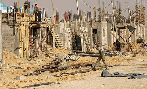 Arab labourers work at the construction site of a residential project for refugees in Rafah in the southern Gaza Strip.
