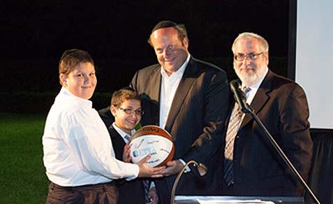 (L-R) Uriel Gurvitz and Yitzy Rosenberg of the Ner Yaakov class; event host Steve Spira receiving a basketball signed by the entire boys class; and Etta Israel's Executive Director Dr. Michael Held.