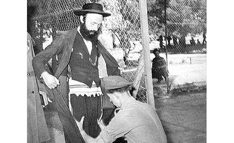 British soldier patting down a Jew in 1947.