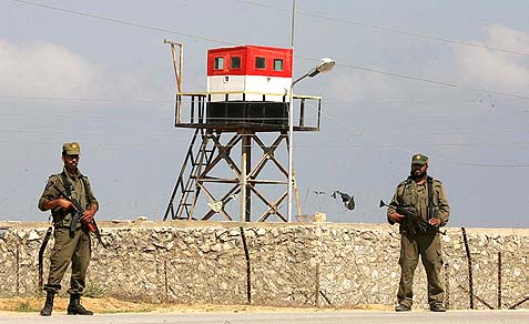 Hamas security stand guard near an Egyptian watch tower on the border with Egypt in Rafah, southern Gaza Strip.