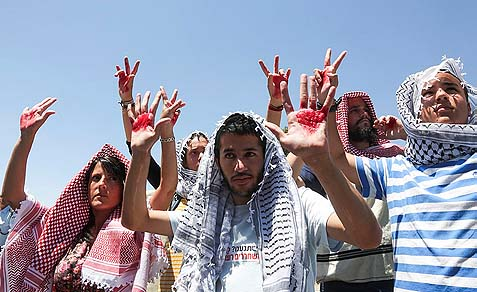 Israelis wearing keffiyehs are holding up their hands which are covered in fake blood, protesting outside the office of Israel's Prime Minister in Jerusalem the release of Arab prisoners with blood on their hands.