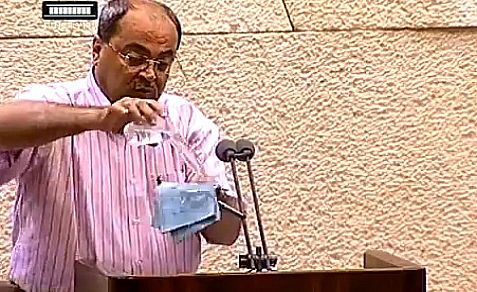 Arab Knesset Member pours water on a proposal law he does not like and damages the Knesset microphone at the same time