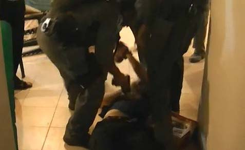 Police tasering a settler in his home, despite the fact that the man is offering no resistance.
